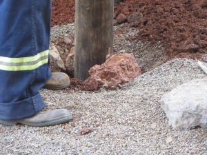 Securing the new pole.  No cement, but rocks firmly imbedded along with the pole keep it secure.