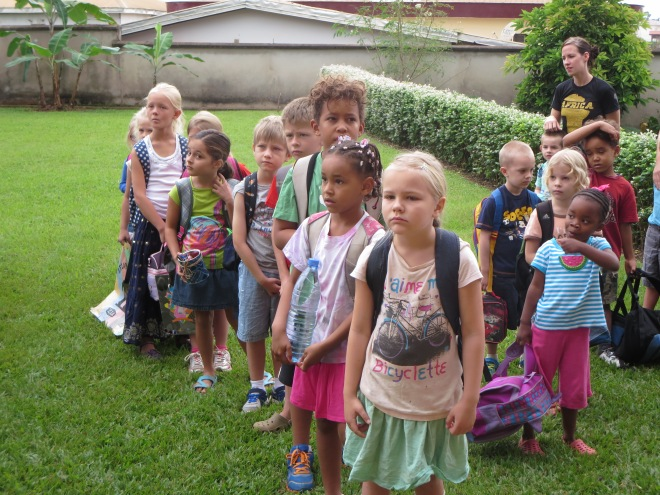 Kindergarten students (on right) and grade 1 & 2 students line up for class.