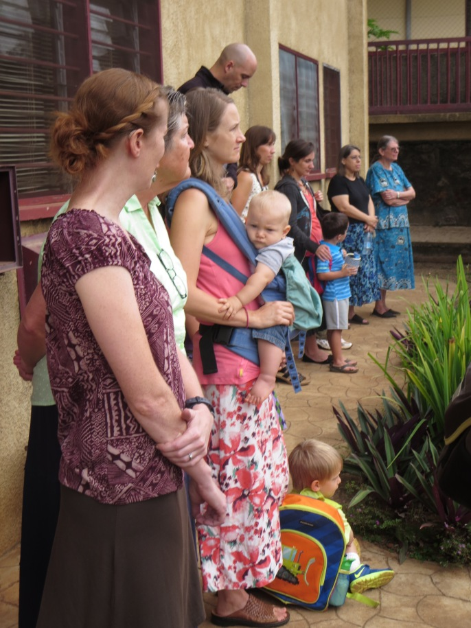 Parents and teachers listen to instructions on the 1st day of school.